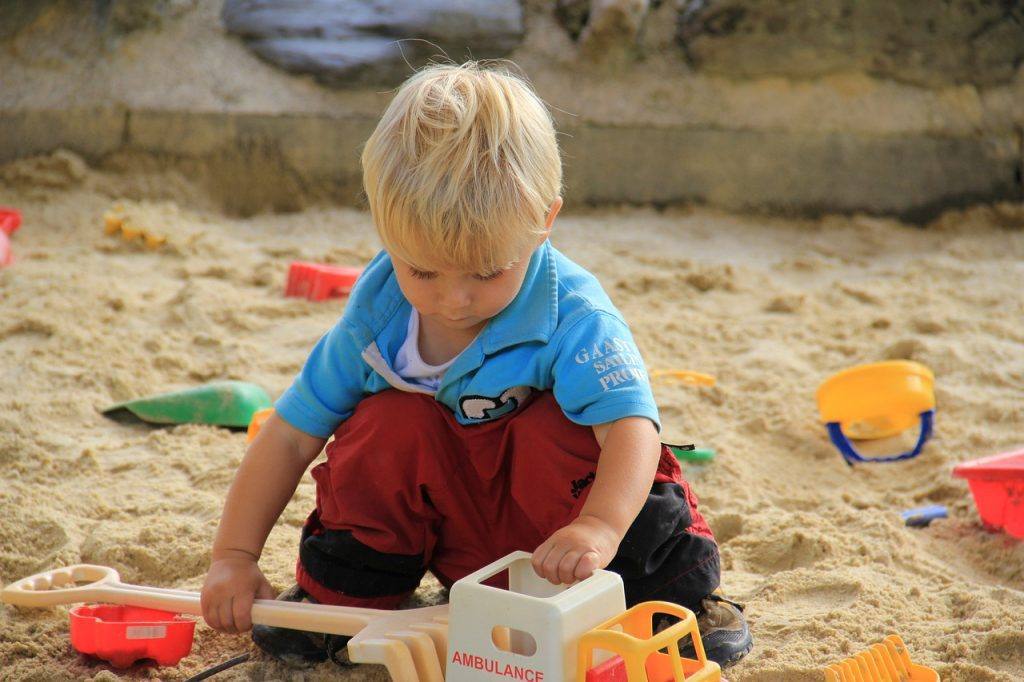 Boy playing in sandpit