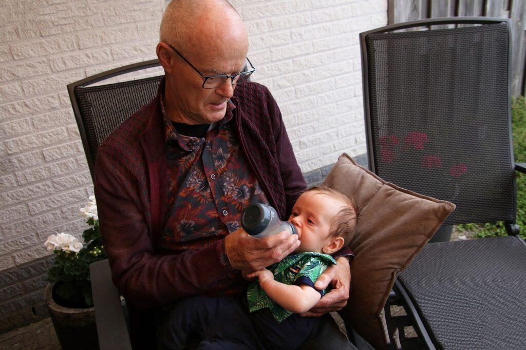 Grandfather feeding baby